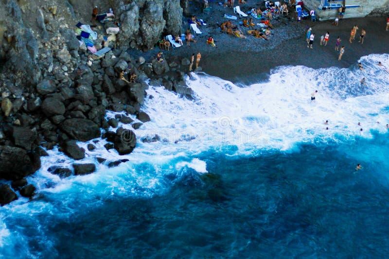 Hoogste mening, mening van de kust van de Zwarte Zee tijdens een hoogtepunt van het onweersstrand van toeristen en vuilnis royalty-vrije stock afbeelding