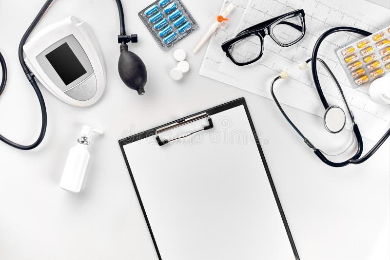Hoogste mening van de lijst van het artsen` s bureau, leeg document aangaande klembord met pen, stethoscoop, elektronische manome stock afbeelding