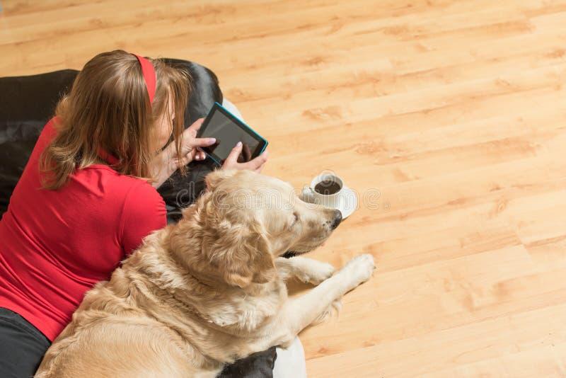 Hoogste mening van de vrouw en de hond die binnen ontspannen stock fotografie