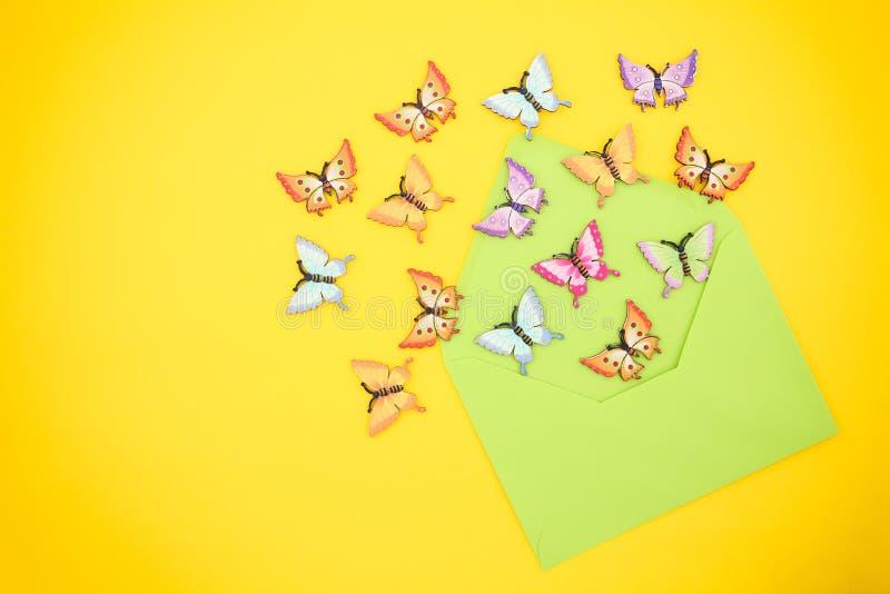 Hoogste mening van decoratieve, multicolored vlinders die uit een open, groene envelop van gerecycleerd document op een trillend  royalty-vrije stock fotografie