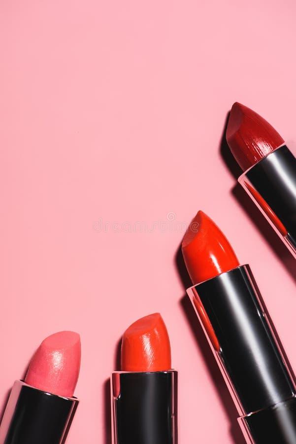 hoogste mening van diverse lippenstiften van rode schaduwen op roze oppervlakte stock foto's