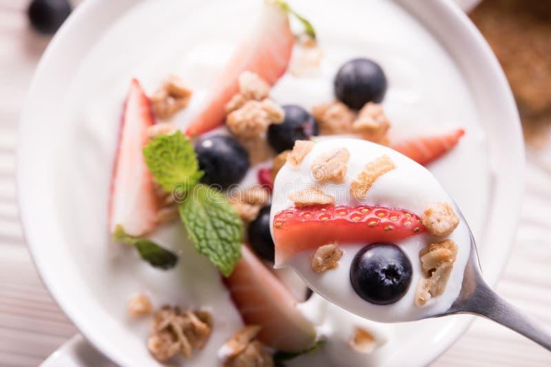 Hoogste mening van duidelijke yoghurt met verse vruchten en granola op bovenkant in lepel en kom op de lijst royalty-vrije stock fotografie