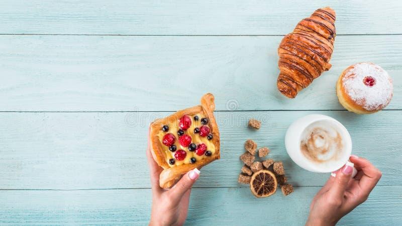 Hoogste mening van een blauwe houten lijst van cakes, cappuccino en meer ontbijt klassiek zoet voedsel stock fotografie