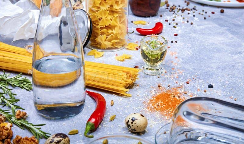 Hoogste mening van een grijze lijst met deegwaren, glasfles, rode Spaanse peperpeper, kwartelseieren en okkernoten op een grijze  stock foto