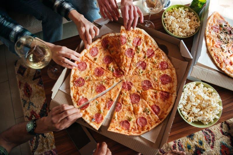Hoogste mening van een groep vrienden die grote pizza eten stock foto's