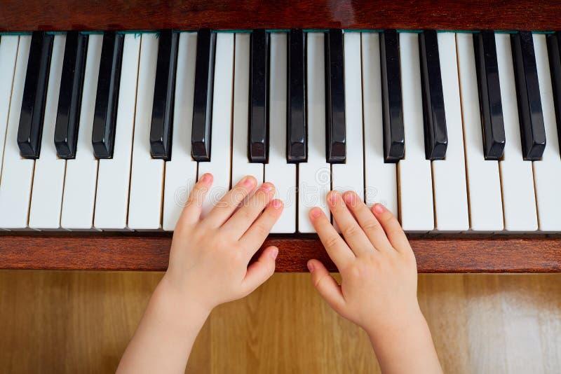 Hoogste mening van een hand, een toetsenbord van de kindpiano De hand o van het kleine kind royalty-vrije stock afbeelding