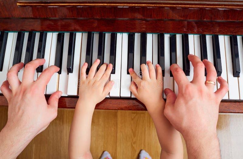 Hoogste mening van een hand, een toetsenbord van de kindpiano De hand o van het kleine kind royalty-vrije stock fotografie