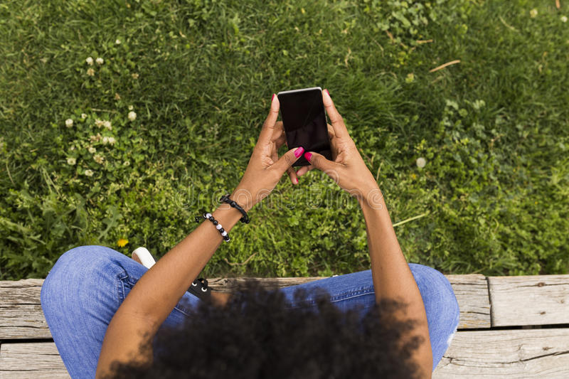 Hoogste mening van een jonge afro Amerikaanse vrouw die mobiele telefoon met behulp van Gree stock fotografie