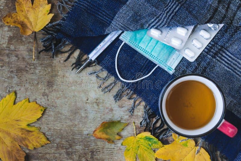 Hoogste mening van een kop thee, een blauwe sjaal, een thermometer, drugs en medische gezichtsmasker en bladeren op houten achter royalty-vrije stock foto