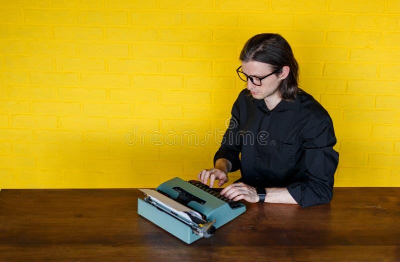 Hoogste mening van een mens in oogglazen, in zwart overhemd, gezet op een lijst, die aan een schrijfmachine, over yellomuur werke stock afbeelding
