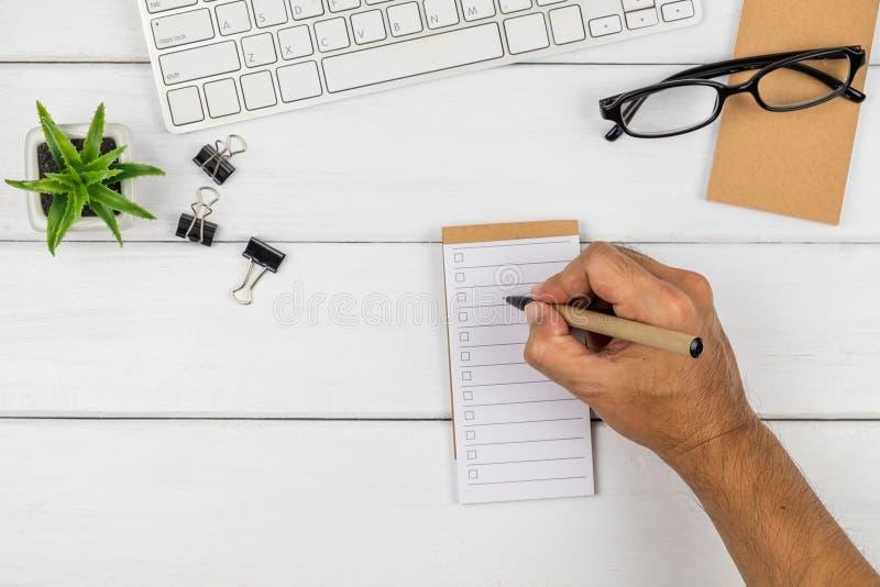 Hoogste mening van een mensen` s hand die op het document van de controlelijst schrijven stock fotografie