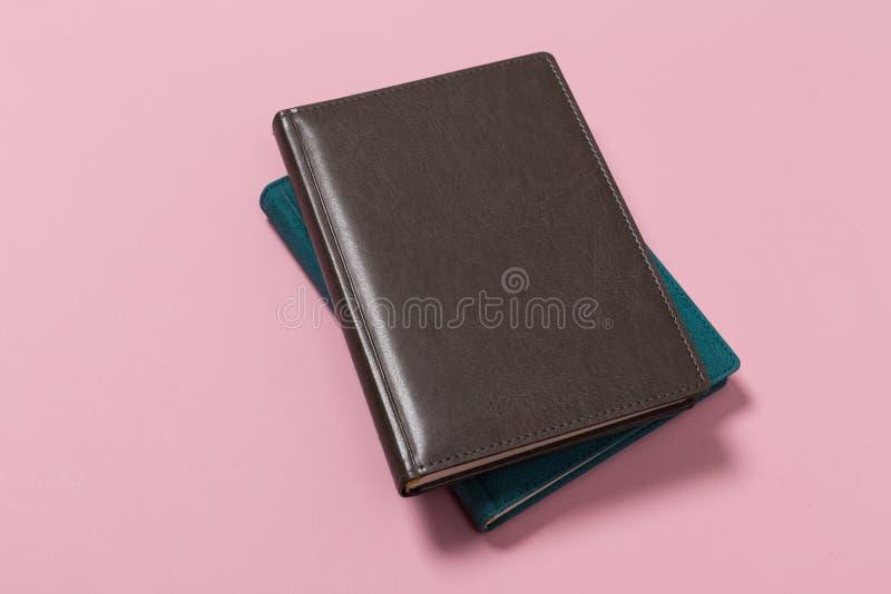 Hoogste mening van een open notitieboekje op een roze achtergrond stock fotografie
