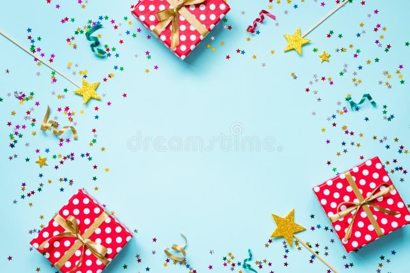Hoogste mening van een rode gestippelde giftdozen, gouden toverstokjes, kleurrijke confettien en linten over blauwe achtergrond H royalty-vrije stock foto