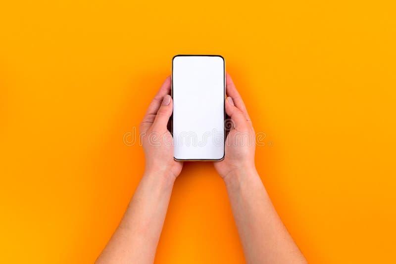 Hoogste mening van een vrouwenhand die telefoon op oranje achtergrond met behulp van stock foto