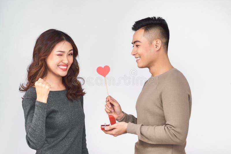 _hoogste mening van gelukkig jong paar kijken bij elkaar en glimlachen Het meisje houdt een rood document hart stock foto