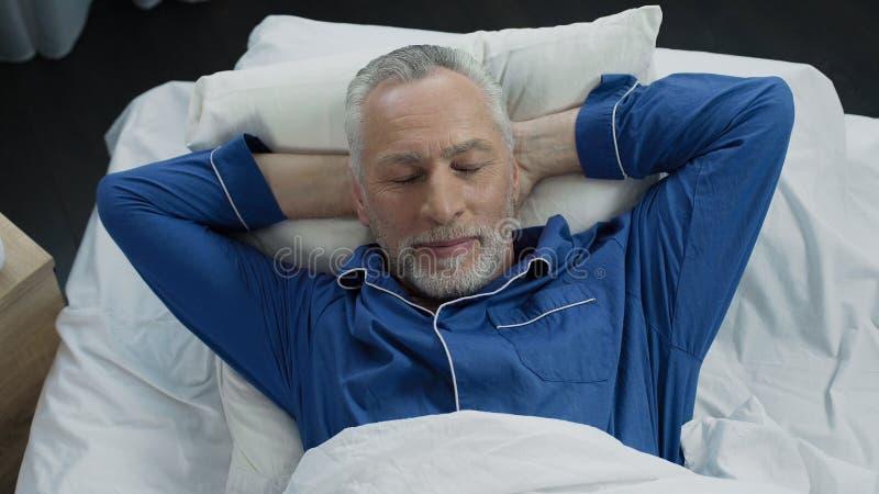 Hoogste mening van gelukkig oud in zijn bed liggen en mannetje die, gezonde slaap, ochtend glimlachen stock afbeeldingen