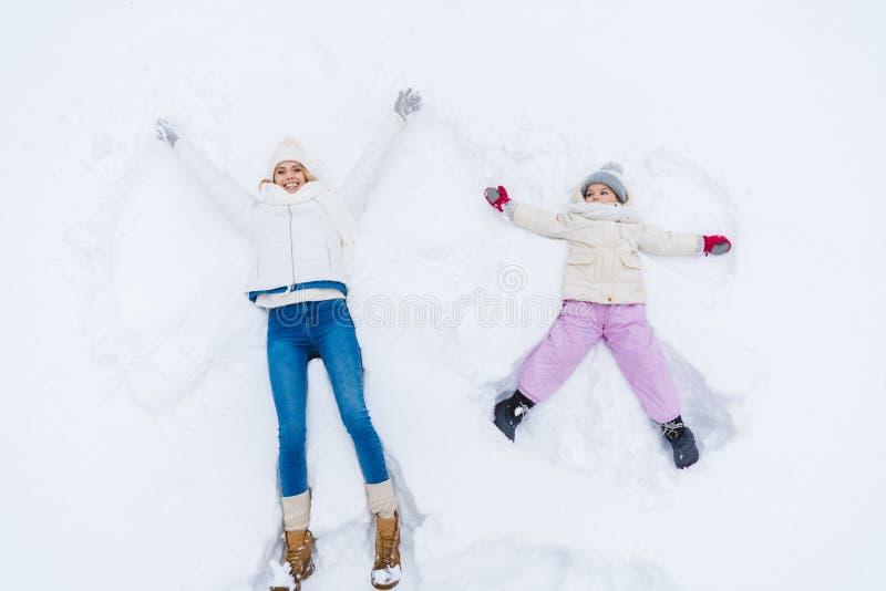 hoogste mening van gelukkige moeder en dochter die sneeuwengelen maken stock illustratie