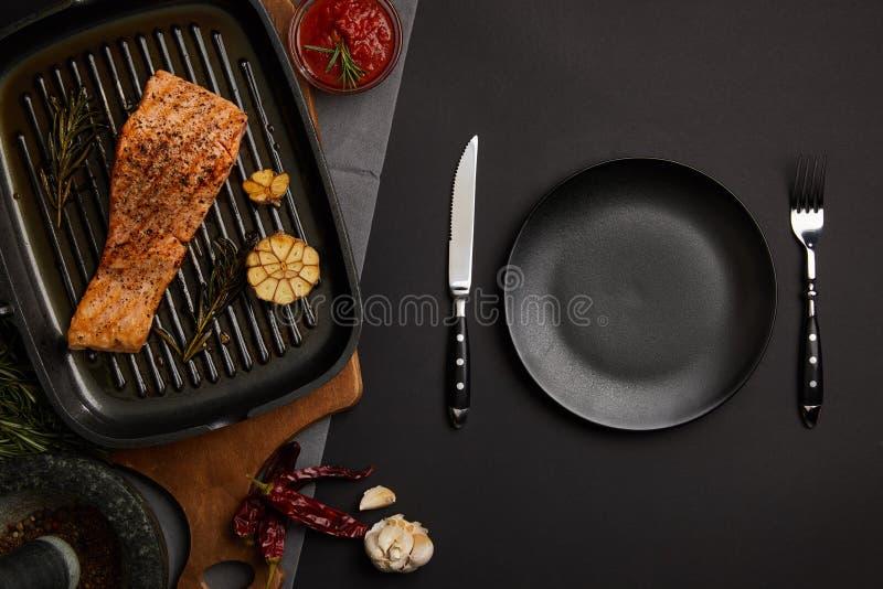 hoogste mening van geschikt geroosterd zalmlapje vlees op houten scherp raad, saus en bestek op zwart tafelblad royalty-vrije stock afbeeldingen