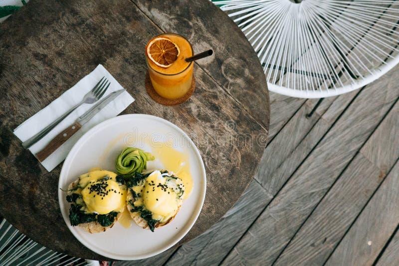 Hoogste mening van Gezond Ontbijt met Broodtoost en Gestroopt Ei met spinazie, avocado op houten lijst Sinaasappel smoothie  stock foto