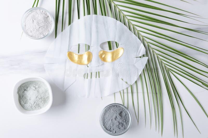 Hoogste mening van gouden oogflarden, gezichtsmasker en kosmetische klei - blauw, wit, zwart en groen blad op witte oppervlakte C stock foto