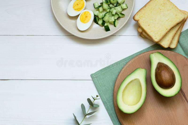 Hoogste mening van graangewassentoost met avocado, kwartelseieren op witte houten raad en ingredi?nten voor toost op witte achter royalty-vrije stock fotografie