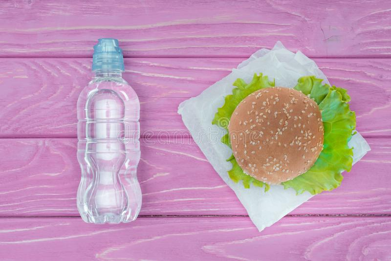 hoogste mening van hamburger en plastic fles water op viooltje stock afbeelding