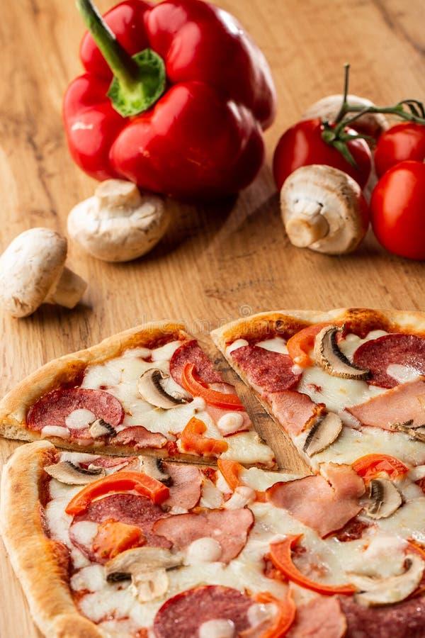 Hoogste mening van heerlijke Capricciosa-Pizza op houten lijst Ingrediënten gepelde tomaat, kaas, ham, paddestoelen, salami royalty-vrije stock foto