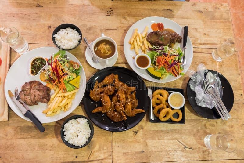 Hoogste mening van het lapje vlees van de varkensvleespeper met groente en frieten en saus en kip wingin en gebraden uien witte p stock afbeelding