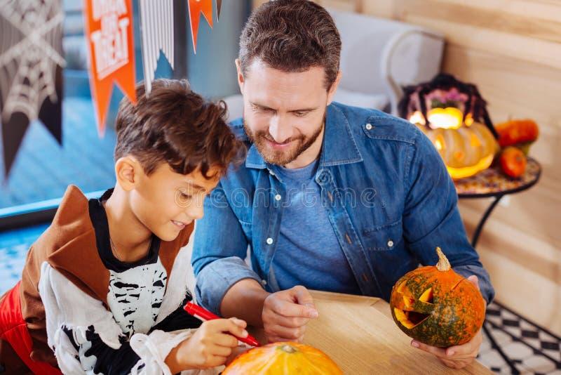 Hoogste mening van het richten van leuke zoon en het houden van vader van kleurende pompoenen voor Halloween royalty-vrije stock foto