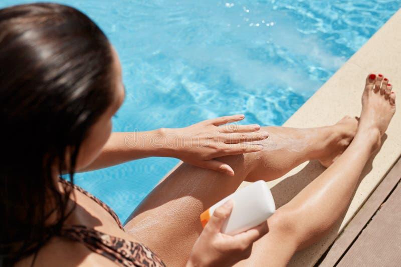 Hoogste mening van het zwarte haired slanke vrouw ontspannen dichtbij zwembad, wat betreft haar benen met hand, die de room van d royalty-vrije stock fotografie