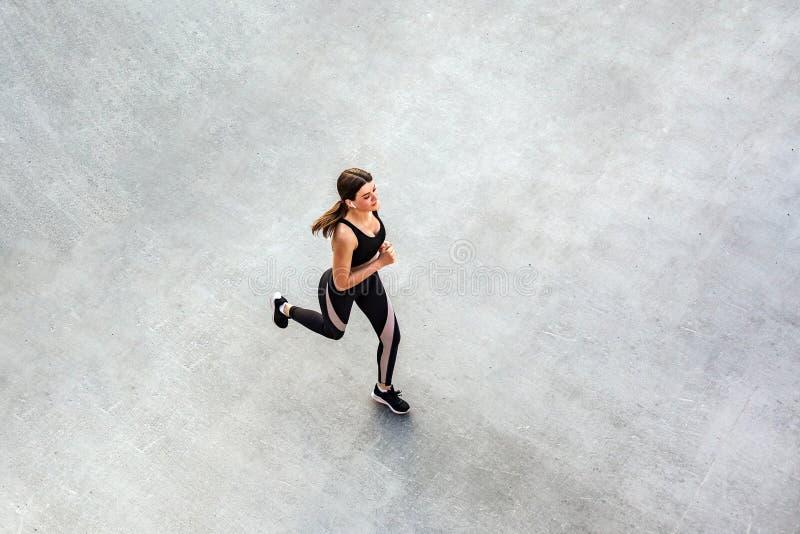 Hoogste mening van jonge aantrekkelijke atletische vrouwensnelheid die op stadsasfalt en training lopen in de ochtendtijd op een  royalty-vrije stock foto's