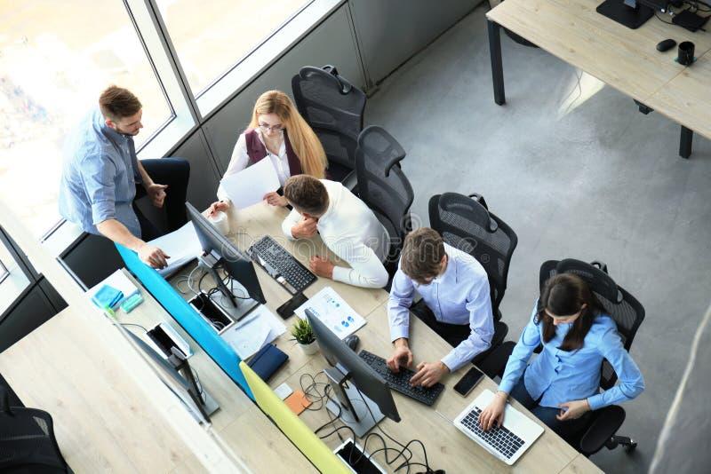 Hoogste mening van jonge moderne collega's die in slimme vrijetijdskleding terwijl bestedende tijd in het bureau samenwerken royalty-vrije stock foto's