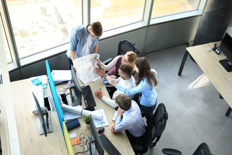 Hoogste mening van jonge moderne collega's die in slimme vrijetijdskleding terwijl bestedende tijd in het bureau samenwerken stock afbeelding