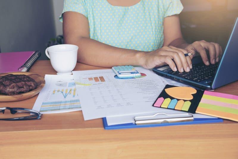 Hoogste mening van jonge werkende vrouw gebruikend laptop en lezend rapport, grafieken, grafieken, document op het werk royalty-vrije stock foto's