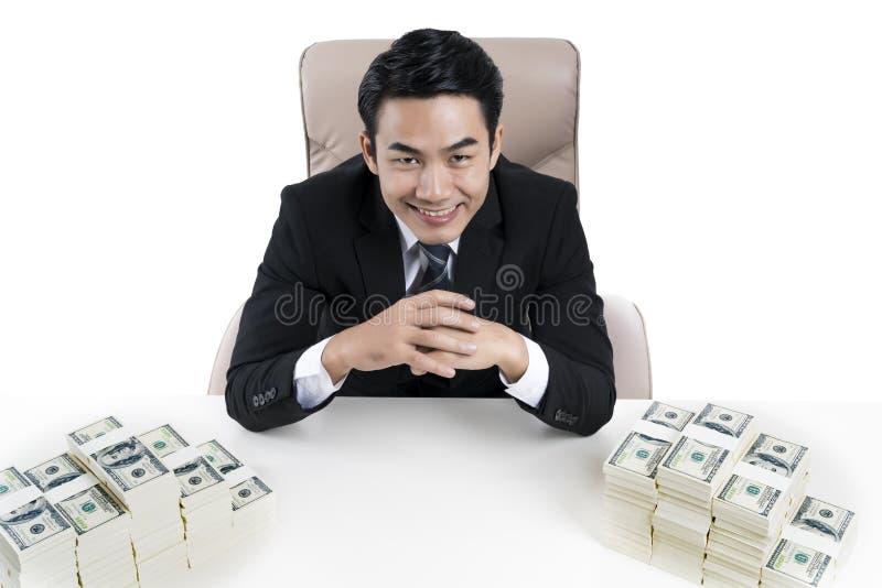 Hoogste mening van jonge zakenman en twee grote stapels van geld op bureau royalty-vrije stock foto's
