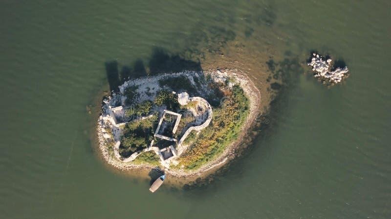 Hoogste mening van klein eiland met ruïnes voorraad Ruïnes van oud die huis op reepje van land door overzees wordt omringd Verget stock afbeelding