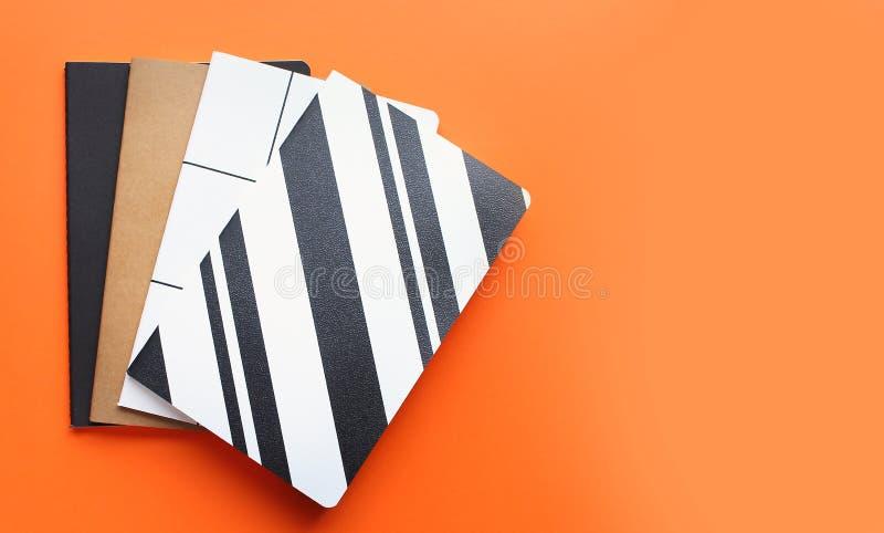 Hoogste mening van kleurrijke notitieboekjes op heldere oranje achtergrond stock afbeelding