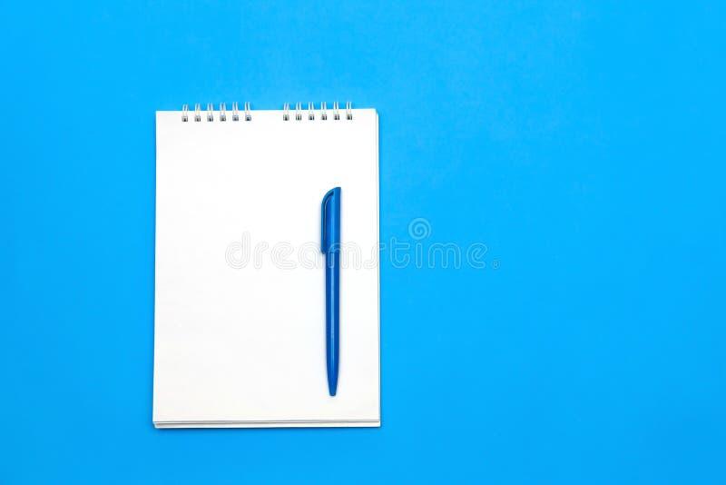 Hoogste mening van leeg notadocument met pen op blauwe houten lijst voor achtergrond stock fotografie