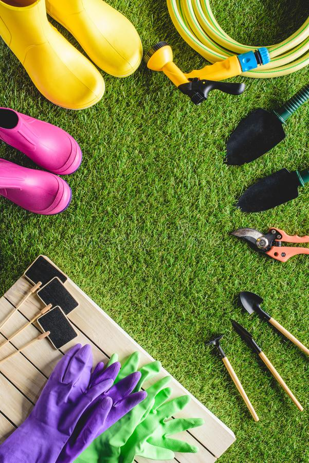 hoogste mening van lege borden, rubberlaarzen, beschermend handschoenen en het tuinieren materiaal stock foto's
