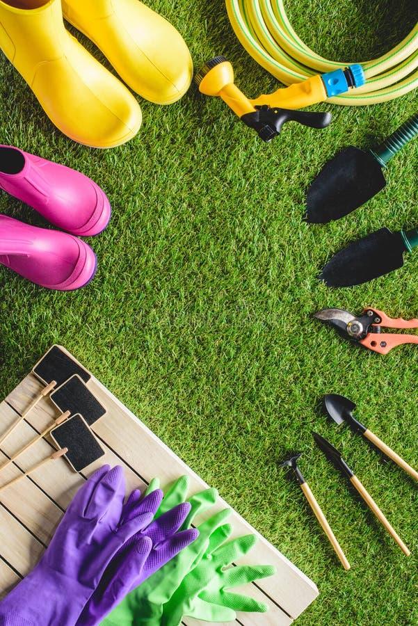 hoogste mening van lege borden, rubberlaarzen, beschermend handschoenen en het tuinieren materiaal op gras stock afbeeldingen