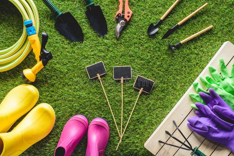 hoogste mening van lege die borden door rubberlaarzen, het tuinieren materiaal en beschermende handschoenen worden omringd royalty-vrije stock fotografie