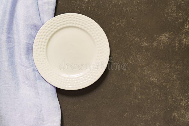 Hoogste mening van lege gediende plaat, blauwe textiel op zwarte concrete achtergrond De ruimte van het exemplaar stock afbeelding
