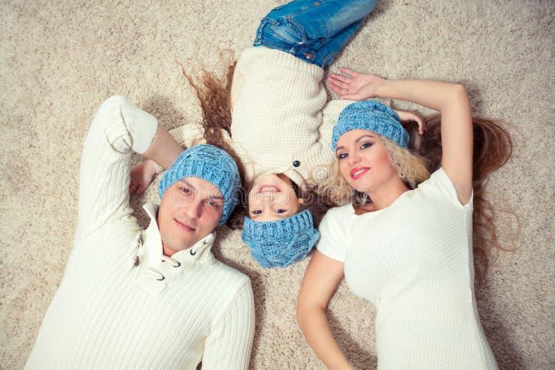 Hoogste mening van leuk camera bekijken en meisje en haar mooie jonge ouders die terwijl het liggen op de vloer bij glimlachen royalty-vrije stock foto's