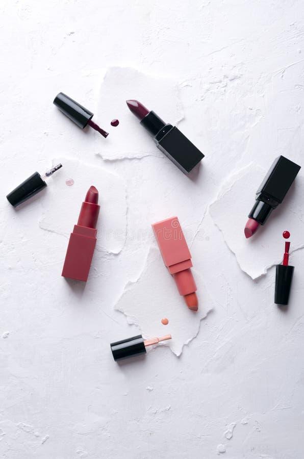 Hoogste mening van lippenstiften en nagellak op de witte oppervlakte Verticaal schot stock afbeeldingen