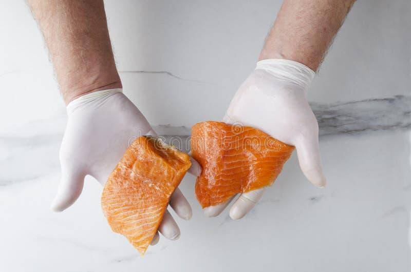 Hoogste mening van mannelijke handen en verscheidene heerlijk, maar ruwe stukken van zalm tegen witte keukenlijst stock fotografie