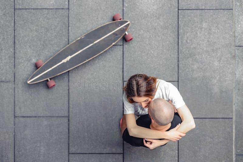 Hoogste mening van modieus paar die koesteren dichtbij longboard stock afbeeldingen