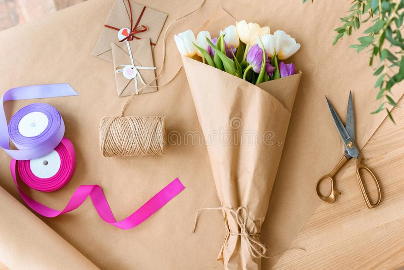 hoogste mening van mooi boeket van tulpen, schaar, linten en enveloppen met kabel stock afbeelding