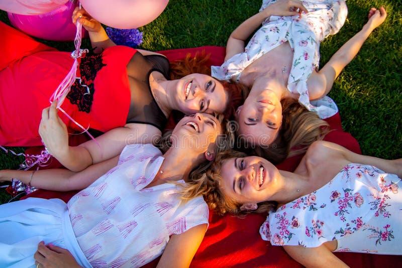 Hoogste mening van mooie modieuze vrienden die terwijl het liggen op gras glimlachen stock fotografie