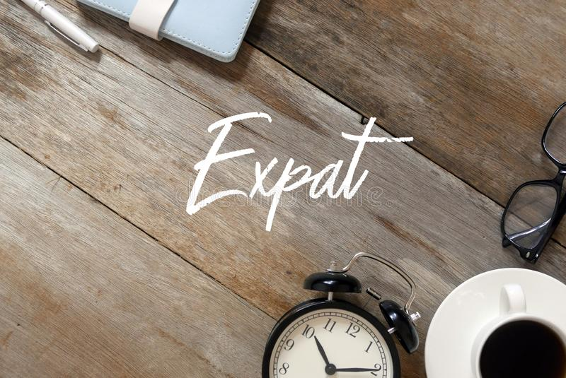 Hoogste mening van notitieboekje, pen, klok, een kop van koffie, zonnebril op houten die achtergrond met Expat wordt geschreven stock afbeelding