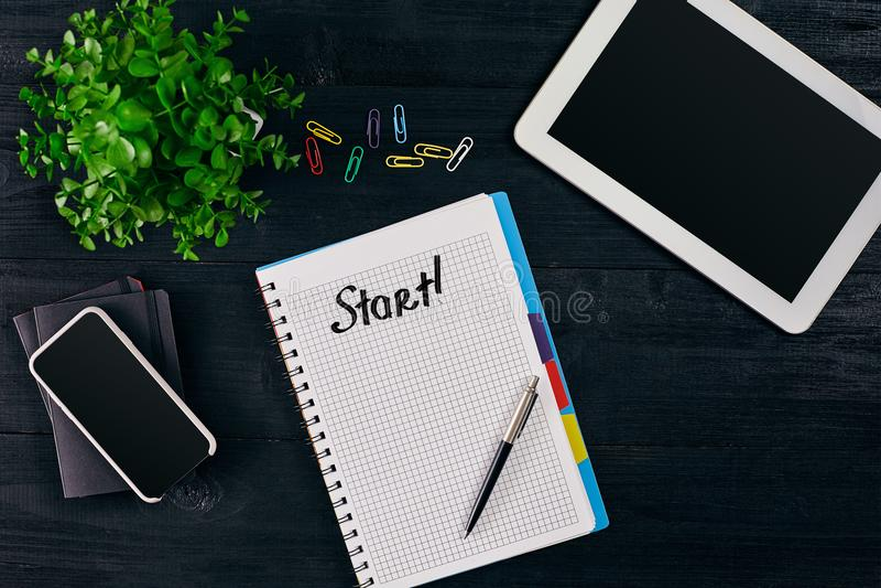 Hoogste mening van open die notitieboekje met BEGINinschrijving wordt geschreven Groene bloem, tablet, gekleurde paperclippen, sl royalty-vrije stock foto's